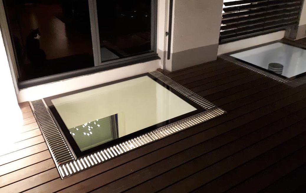 Zwei beleuchtete, begehbare Lichtschächte auf der Terrasse