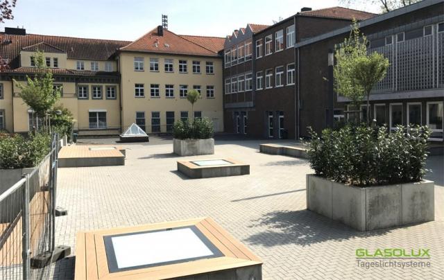 Quadratische, begehbare Oberlichter als Sitzflächen auf einem Schulhof
